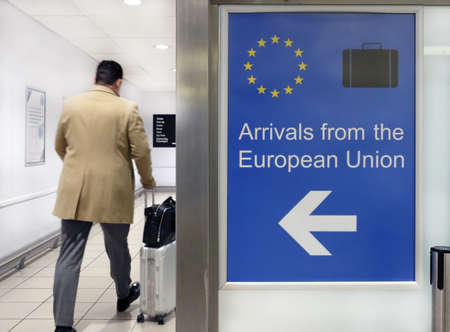 A wide angle shot of an airport sign welcoming people arriving from the European Union next to a person