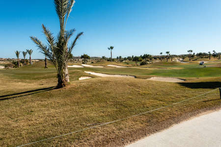 A gold course with trees and pathways under a clear blue sky in Spain