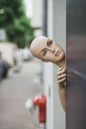 A vertical shot of female mannequin near a black wall