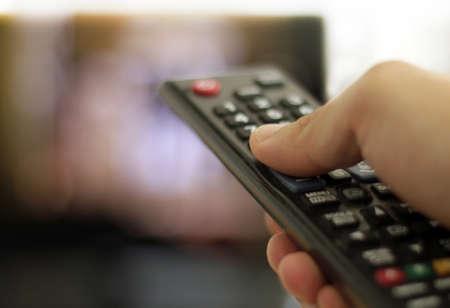 A closeup shot of a man holding a black remote control