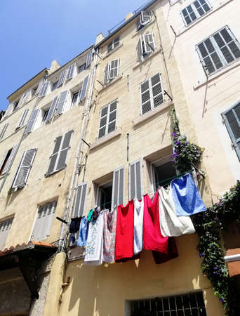 A low angle view of an apartment building with clothes hanging from the ropes in Marseille in France 写真素材