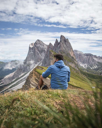 A shot of a man looking at the valley and mountains of Puez-Geisler Nature Park, Italy