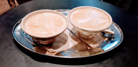 A closeup shot of two cups full of coffee on a silver tray 스톡 콘텐츠