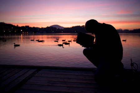The silhouette of a man reading a book on a wooden bridge surrounded by the lake during the sunset