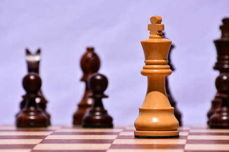 A selective focus shot of a king chess piece in a chessboard with a blurred background