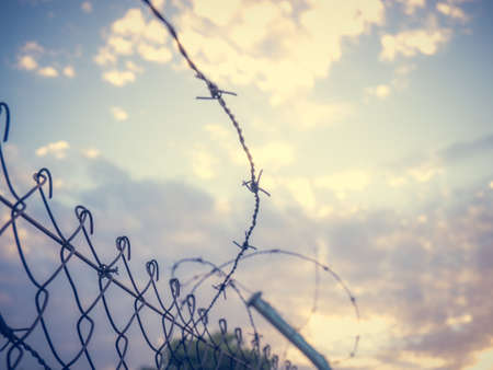 A low angle shot of barbed wire under a cloudy sky