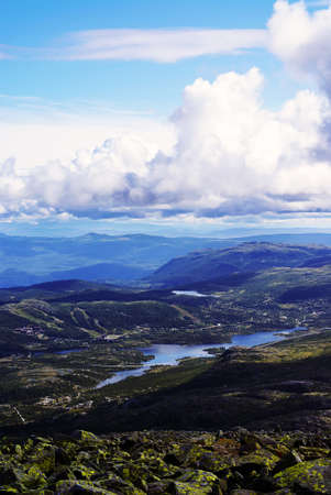 A vertical high angle shot of the hills under the cloudy sky in Tuddal Gaustatoppen, Norway