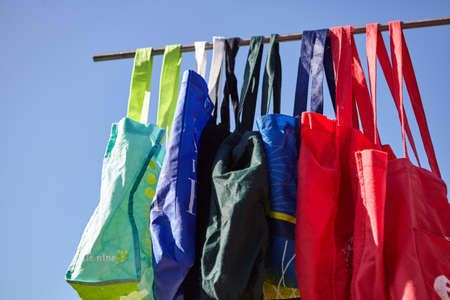 A low angle shot of colorful eco-friendly reusable cloth bags hanging on a pole - no plastic concept