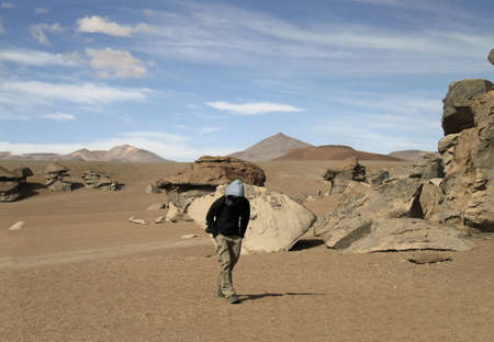 A wide angle shot of a man walking next to cliffs on a desert