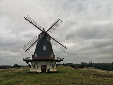A wide angle shot of a windmill under a sky full of clouds