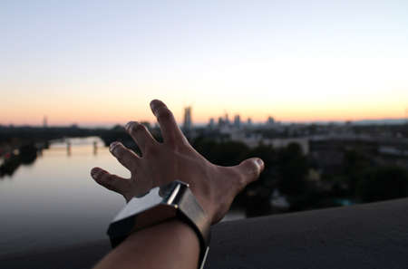 A wide angle shot of a man's hand with the background of the city