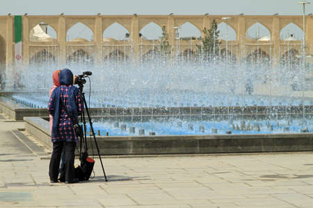 A wide angle shot of two people taking a photo of the fountains