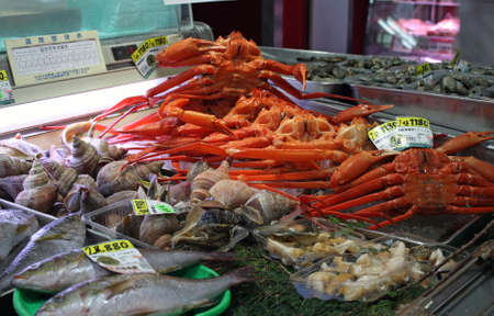 A wide angle shot of fish, crabs and other types of seafood on the market 写真素材