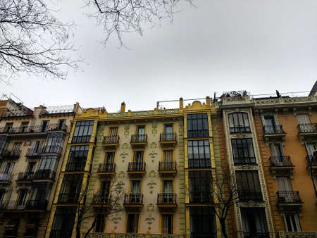 A low angle shot of a building in Spain under a cloudy sky