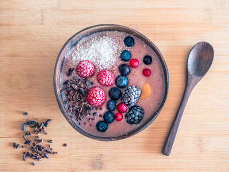 A high angle shot of a bowl of muesli with berries on a wooden surface