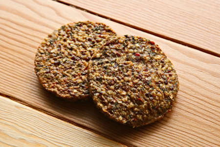 Vegan burger patties made from quinoa, lentils and beans on a wooden cutting board.