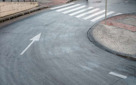 A high angle shot of a road curve with a white directional arrow and pedestrian crossing 写真素材