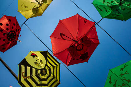 A low angle shot of colorful umbrellas hanged on the wires in the air