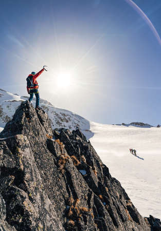 Climber or alpinist at the top of a mountain. Success of mountaineer reaching the summit. Outdoor adventure sports in winter alpine moutain landscape Zdjęcie Seryjne