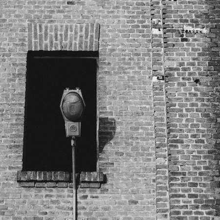 A grey-scale shot of a street lamp in front of an old building with a broken window Stockfoto