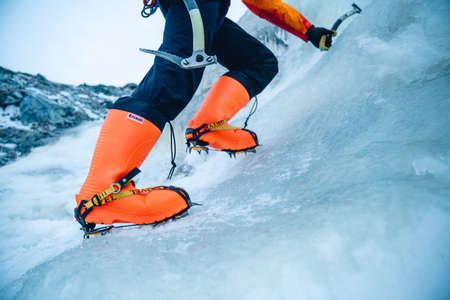 A closeup shot of an orange ice climbing boots with crampons  attached