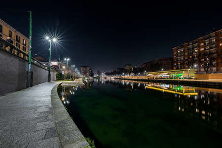 A beautiful shot of a clear night sky with city lights in the dock of navigli in milan italy