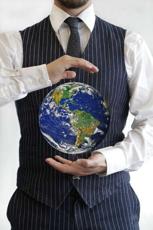 A vertical shot of a well-dressed male with a picture of the earth in the middle of his hands