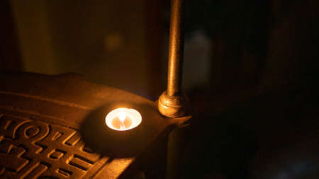 A dramatic setting of a closeup shot of a candle on a step with a single baluster in the background Stock Photo