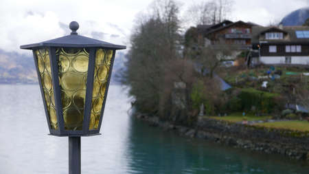 A selective shot of a yellow and black lamp with a river and a house in the background