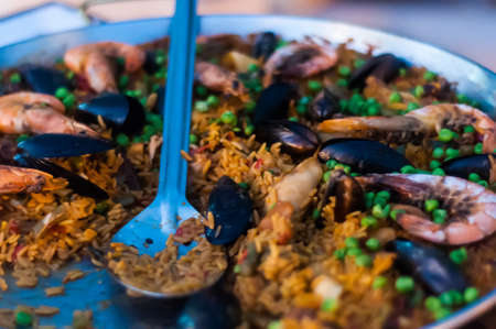 A blue plastic spoon in a plate with paella with seafood