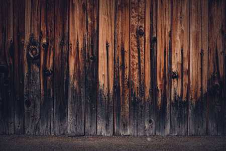A closeup shot of a wood fence with charred base Standard-Bild