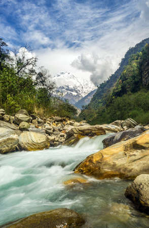 A vertical shot of a rapid river crashing on the rocks with mountains in the background 免版税图像