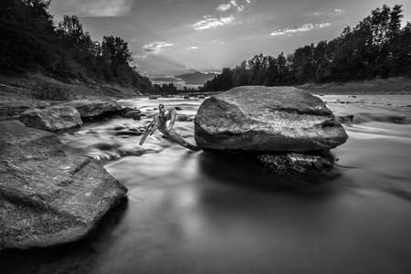 A grayscale shot of a rock in the water stream surrounded by trees