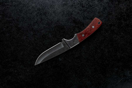 A closeup shot of a small sharp knife with a brown handle  on a black background