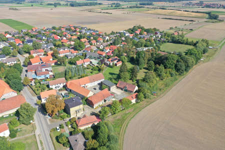 A top view shot of a village surrounded by plowed fields 写真素材