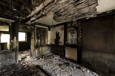 An inside shot of an abandoned destroyed building with burned walls and worn-out doors Banque d'images