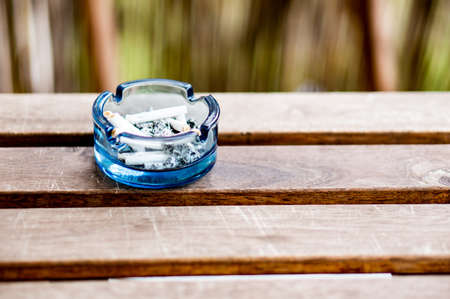 A blue ashtray on a wooden bench in the park Foto de archivo