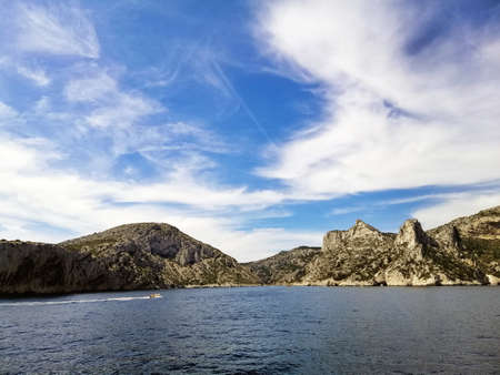 The Massif des Calanques surrounded by the sea under a blue sky and sunlight in France