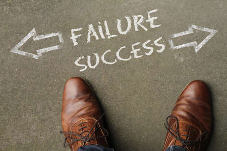 A high angle shot of failure and success marked with opposite directions on the ground