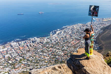 CAPE TOWN, SOUTH AFRICA - Dec 27, 2019: An African women sits on a cliff on at the top of Lion's head mountain. This is a popular tourist attraction in the city. Publikacyjne