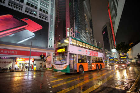 HONG KONG, BOTSWANA - Mar 04, 2019: Double decker buses drive on the road of Causeway Bay on a rainy evening.