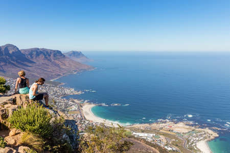 CAPE TOWN, SOUTH AFRICA - Dec 23, 2019: Two hikers sit on a cliff and enjoy the panoramic views on top of Lions head mountain. This is a very popular tourist attraction in the city.