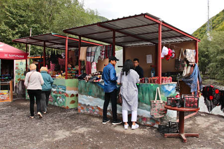 PASANAURI, GEORGIA - Sep 22, 0219: Tourists buying some Georgian food from a road side shop next to the black and white Aragvi river.