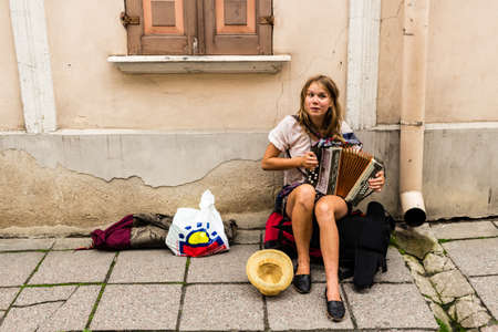 TALLIN, ESTONIA - Sep 05, 2019: A female street musician plays the accordion on a side walk in the old town of Tallin in Estonia.