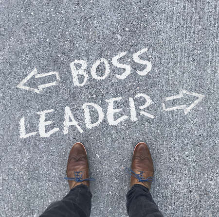 A high angle shot of arrows and the words Boss, Leader written  in front of a man's shoes Stockfoto