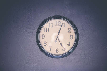 A watch hanging on the wall displaying five o'clock Imagens
