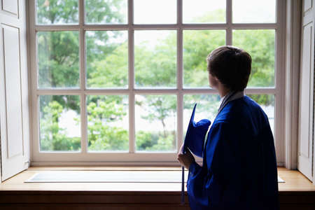 A male in a blue mantle looking out of the window at the graduation day