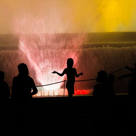 A silhouette of people standing near a water fountain