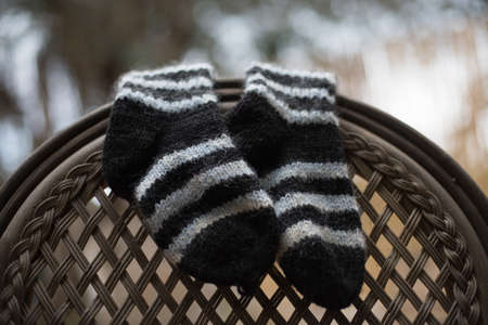 A closeup shot of striped socks hanged on the back of a chair