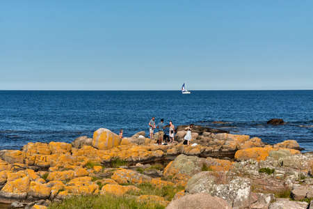 AARSDALE, DENMARK - Jun 28, 2019: Aarsdale, Bornholm island, Denmark - June 28, 2019. Group of tourists spending their time on rocky coast of Baltic sea in Aarsdale.